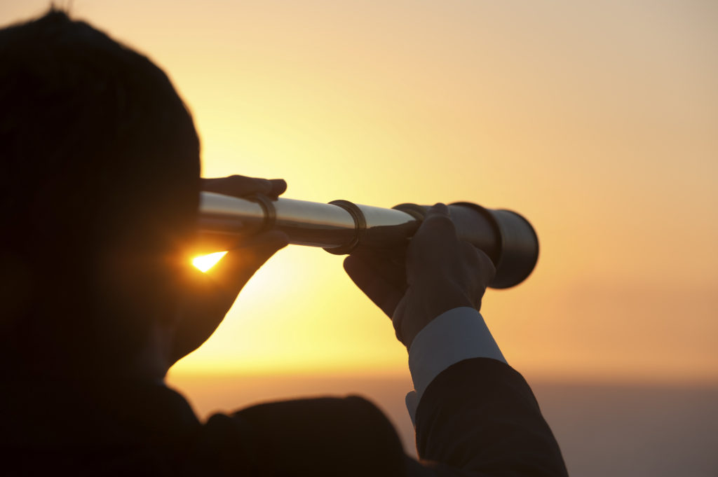 Businessman looking to the future with telescope at sunrise
